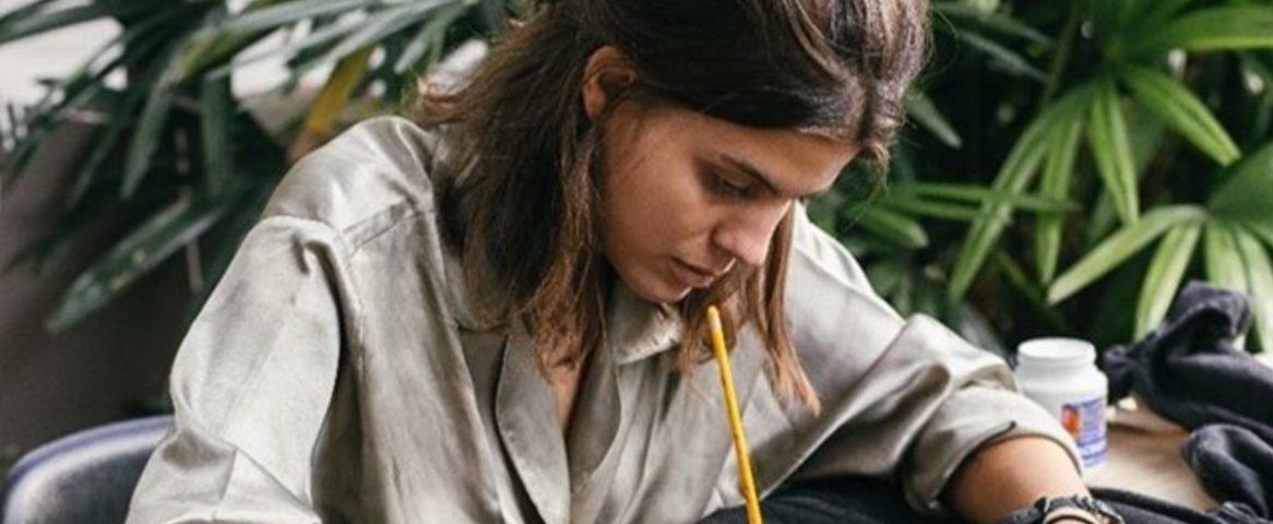 Jovem pinta uma roupa com tinta e pincel.