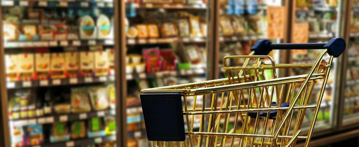 Carrinho de supermercado com diversos produtos ao fundo