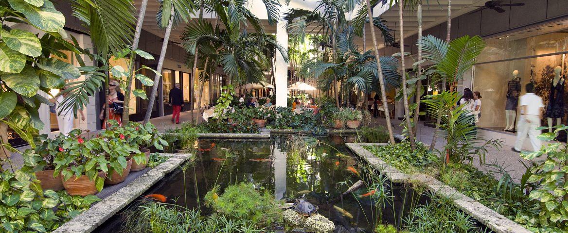 Um dos jardins do shopping Bal Harbour, um dos centros comerciais de luxo mais importantes dos Estados Unidos, em Miami. O jardim possui um lago no meio, onde há peixes. Diversas plantas e vasos estão dos lados do lago. Ao fundo é possível ver algumas lojas.