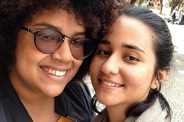 Silvelena e Quezia estão abraçadas. Elas sorriem para a câmera. Silvelena tem pele negra e cabelo afro cortado curta. Usa óculos. Quezia tem pele clara e cabelo preto liso
