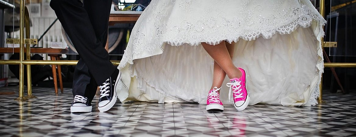 Detalhe dos pés de dois noivos jovens, ambos com tênis. O novo está de terno preto e tênis também preto. E a noiva com roupa tradicional branca, mas calçado cor de rosa, no estilo All Star