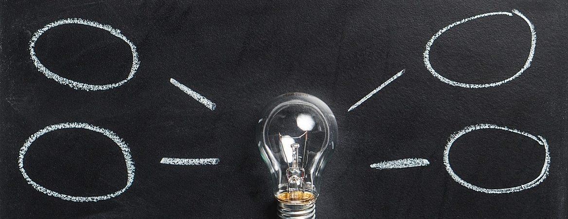 Desenhados em um quadro negro estão uma lâmpada e quatro formas ovais representando ideias