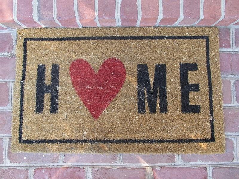 Tapete tipo capacho aparece em close, com a palavra Home, casa em ingl~es, CapaT