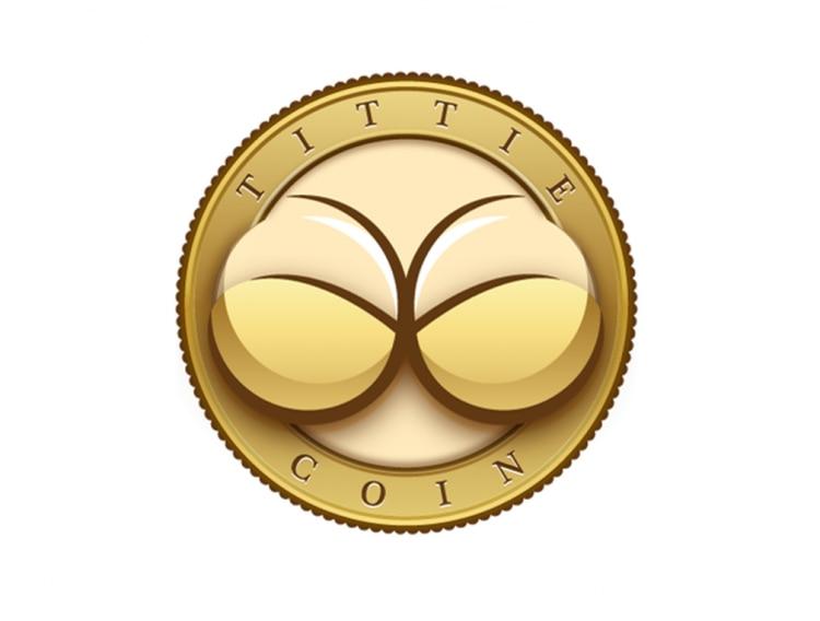 Símbolo da criptomoeda Tittie Coin é o desenho de dois seios, parcialmente cobertos por um sutiã bege. Ao redor do desenho, há uma borda dourada, com o nome da criptomoeda escrito.
