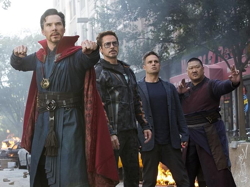 Juntos em Nova York, tendo fogo ao fundo, estão Doutor Estranho, com roupa azul escura e capa vermelha, o Homem de Ferro, vestido com roupa preta e de óculos, Hulk, na versão humana, de blusa preta e blazer cinza, e Wong, de samurai