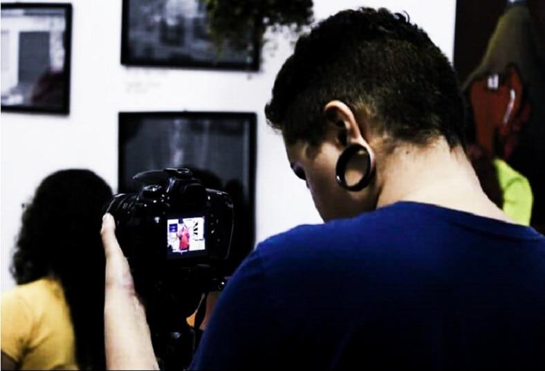 A fotógrafa Damaris Belchior olha pelo visor de uma câmera, esta apoiada por um tripé, em um de seus trabalhos temporários como cinegrafista.