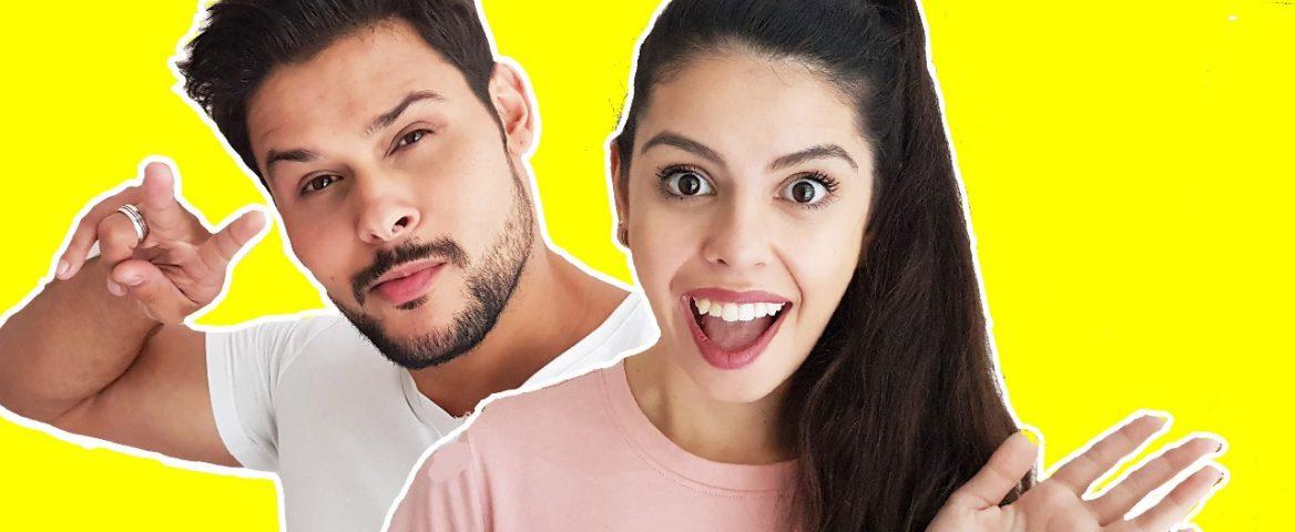Na frente de um fundo amarelo, Filipe Rodrigues e athalia Blandy aparecem sorrindo. Ele tem cabelo curto e barba preta. Ela tem cabelo longo, preto, preso num rabo de cavalo.